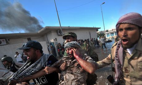 NTC fighters evacuate a wounded comrade during battles in Sirte, Libya