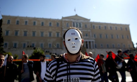 A demonstrator stands in front of the Greek parliament in Athens as a two-day general strike begins