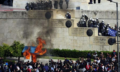 Protesters burn a guard box in front of the Greek parliament in Athens during a two-day strike
