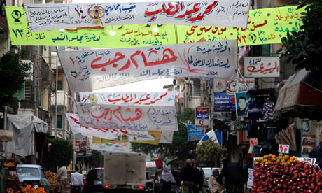 People walk past electoral banners in Alexandria, Egypt