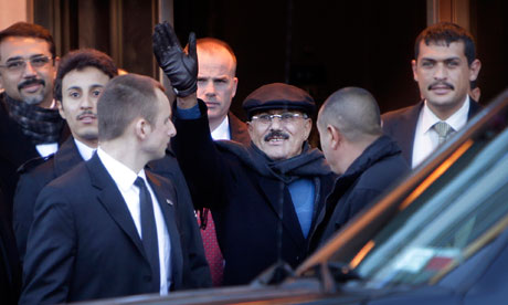 Yemeni President Ali Abdullah Saleh waves to protesters as he leaves his hotel in New York