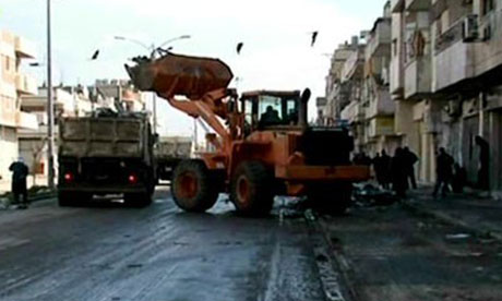 Debris being removed from the streets in Homs, Syira