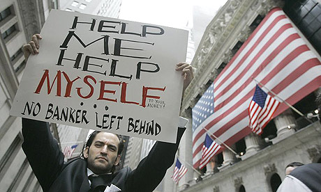 A protestor holds a sign as he marches past the New York Stock Exchange during a rally against the Wall Street bail-out.