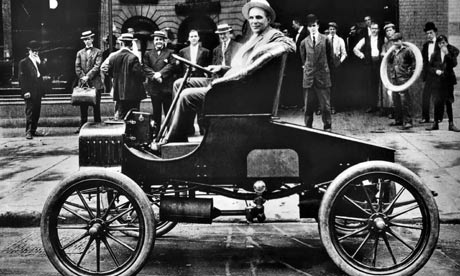 Henry Ford  in his new T Ford model in front of his car plant in Detroit