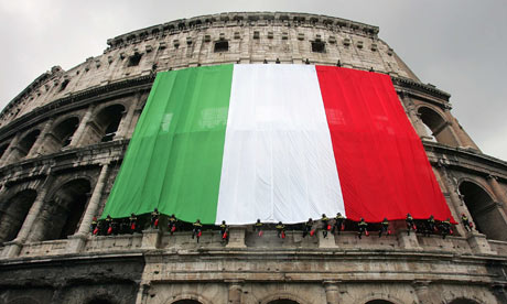 An Italian flag hangs from the side of the Colosseum in Rome