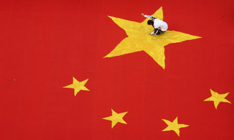 A student embroiders a five-pointed star on a huge Chinese national flag in Jinan, China.