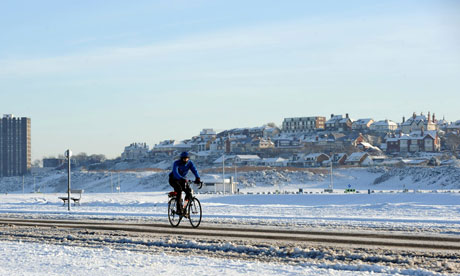 A man cycles along a snow-covered road in New Brighton near Liverpool.