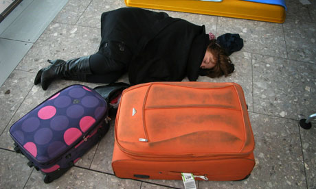 A passenger rests on the floor of terminal five at Heathrow airport