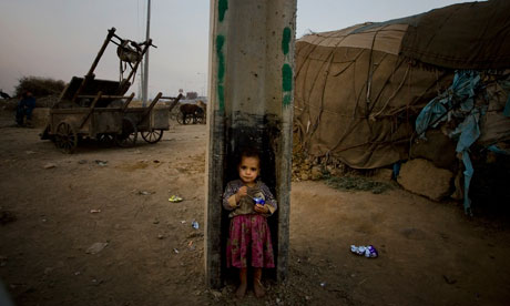 A Pakistani girl eats biscuits while she stands in the gap of concrete pole at a slum area