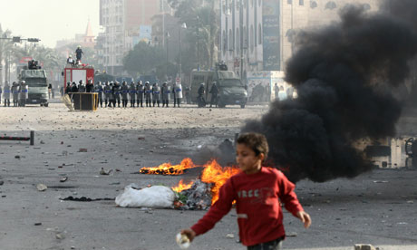 A child walks past burning tyres as demonstrators battle police during a demonstration in Suez