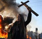 An activist holds up a crucifix as a barricade burns during evictions from Dale Farm travellers camp