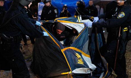 Police officers arrests an Occupy Oakland demonstrator inside a tent
