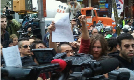 Occupy protesters hold up copies of court order against eviction of Zuccotti Park.