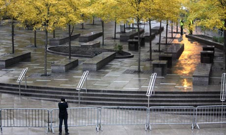 A pedestrian takes a picture of an empty and closed Zuccotti Park in New York