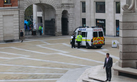 A man smokes a cigarette inside the cordoned-off Paternoster Square, just outside Occupy London camp