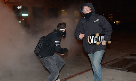 Occupy Oakland protesters running from teargas