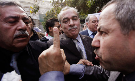 A Syrian protester attacks a member of Syrian opposition delegation in Cairo