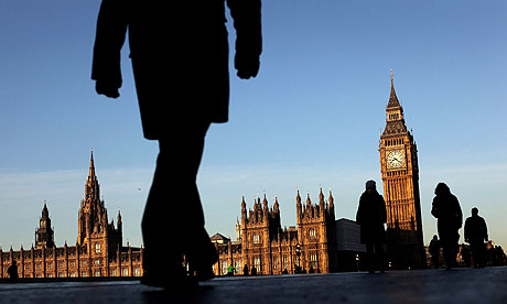 Commuters walk past the Houses of Parliament