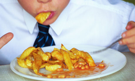 Boy eating a plate of chips and beans