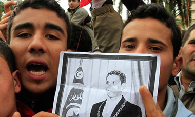 Tunisian protesters chant slogans as they hold a photograph of Mohamed Bouazizi