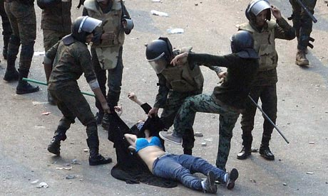Egyptian army soldiers beat a female protester during clashes at Tahrir Square, Cairo