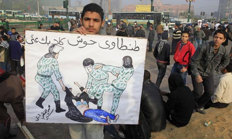 An Egyptian protester holds a sketch of a woman being beaten by Egyptian soldiers.