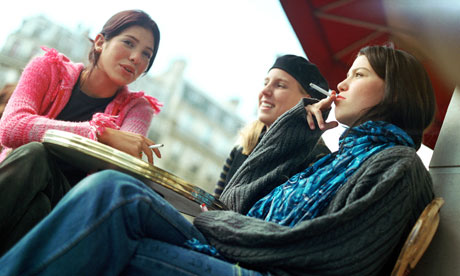 Three teenage girls sitting at cafe terrace, smoking cigarettes, low angle view