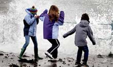 Children dodge waves in Scotland