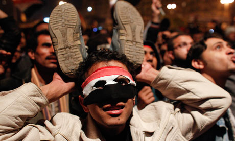 An anti-government protester holds up his shoes as people react to Hosni Mubarak's statement