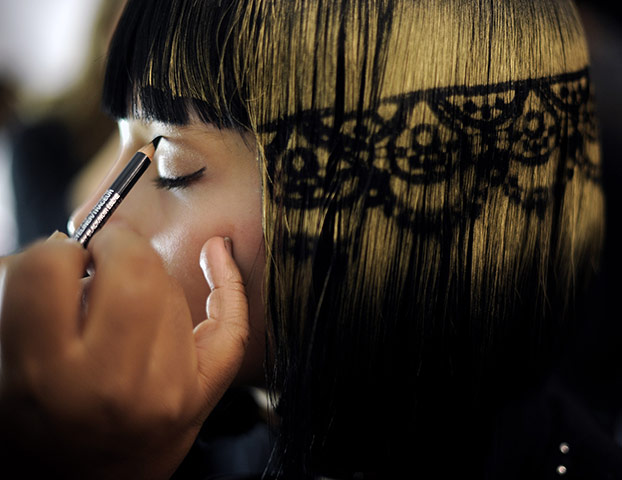 New York Fashion Week: A model with stenciled hair has makeup applied