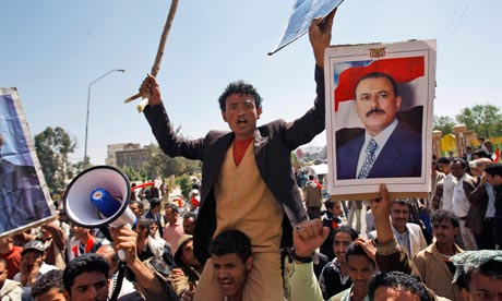 Supporters of the Yemeni government shout slogans as they try to enter Sana'a University