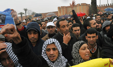 Moroccans raise their hands during a protest demanding broad political reforms, in Rabat, Morocco