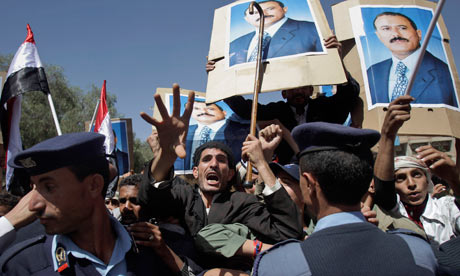 Yemeni policemen push back government supporters at a protest in Sanaa, Yemen