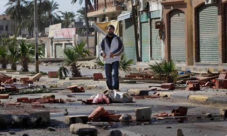 A man walks through roadblocks made by residents in the Tajoura district of eastern Tripoli, Libya