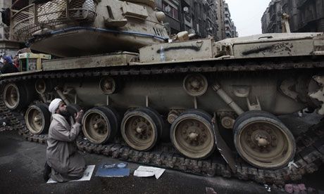 An Egyptian anti-government protester prays next to an army tank in Cairo's Tahrir Square