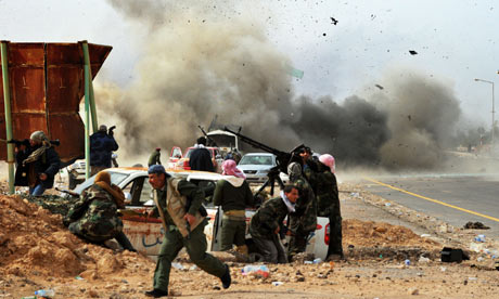 A tank shell explodes near Libyan rebel fighters trying to hold Ras Lanuf