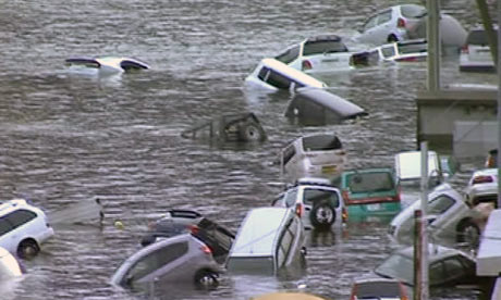 Vehicles are washed away by tsunami in coastal area in eastern Japan