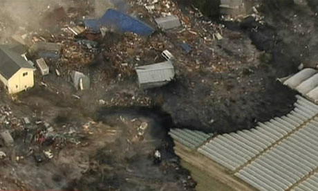 Houses are washed away by tsunami in Sendai, eastern Japan