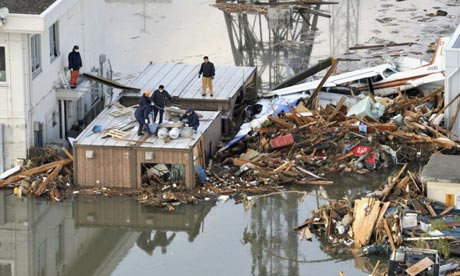 Japan tsunami: people build a raft on the roof of a building