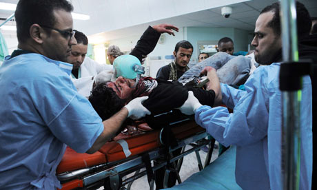 Libyan medics tend to a rebel fighter who was wounded during clashes at Ajdabiya