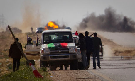 Libyan rebels stop on the road as mortars fire near Ajdabiya