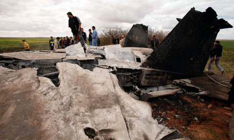 People look at a US Air Force F-15E fighter jet after it  crashed near Benghazi