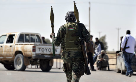 A Libyan rebel fighter carries rocket-propelled grenades at a checkpoint near Ajdabiya