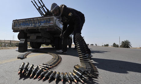 Libyan rebel fighters prepares an anti-aircraft machine gun at a check point near Ajdabiya
