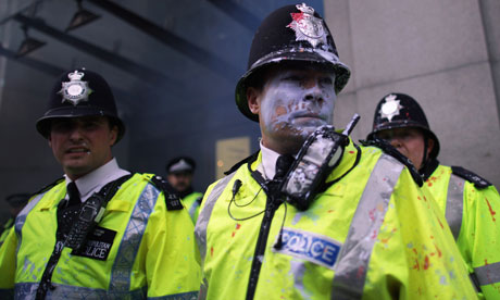 Paint-splattered police look on as protesters attack Topshop during the anti-cuts march in London