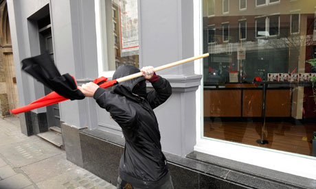 A protester tries to break a window in Oxford Street during the anti-cuts march
