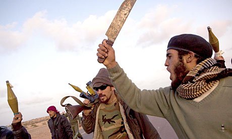Libyan rebel fighters on the road in Bin Jawad, where there has been fierce fighting