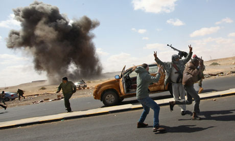 Rebel fighters run as their position is bombed near Ras Lanuf, Libya