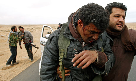 Injured rebels are helped out of a car during a battle between Ras Lanuf and Bin Jiwad, Libya