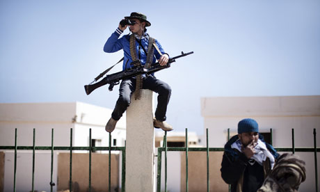 A rebel fighter uses binoculars to monitor the skies over the flashpoint town of Ras Lanuf, Libya